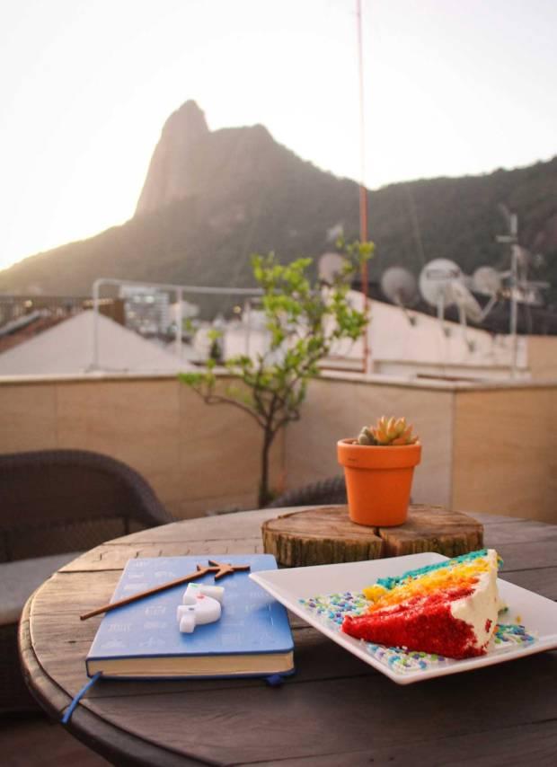 caderno e fatia de bolo em cima de uma mesa redonda e o morro corcovado ao fundo