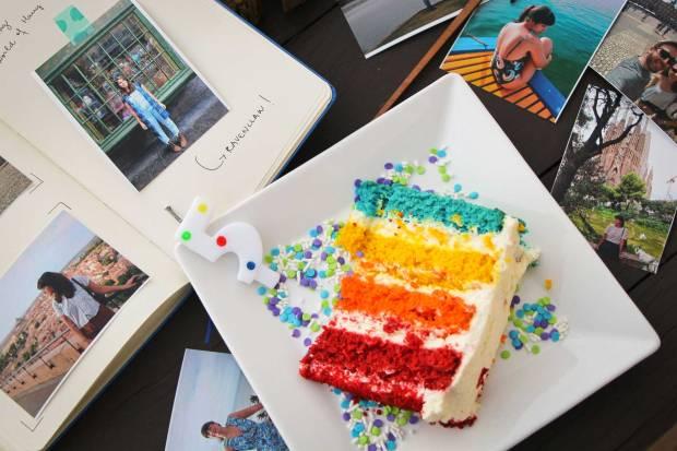 fatia de bolo colorida com uma vela de 5 anos ao lado de fotos de viagem